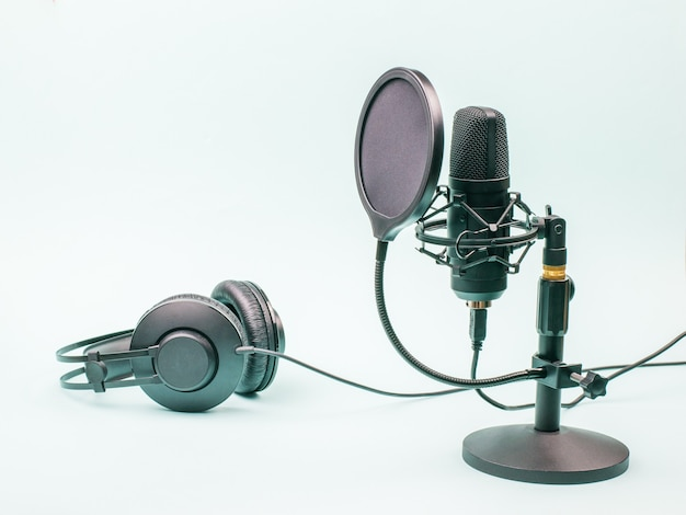 Condenser microphone and wired headphones on a blue background. equipment for recording and reproducing sound.