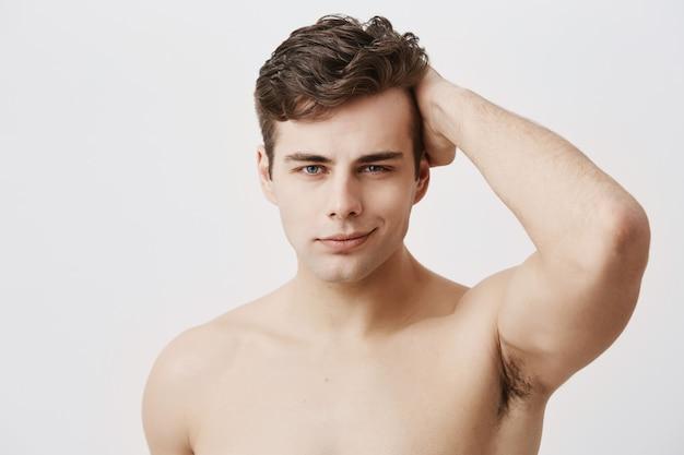 세련 된 머리와 매력적인 눈을 가진 condifent 젊은 유럽 남자, 벌 거 벗은, 검은 머리를 만지고, 포즈. 건강하고 깨끗한 피부가 부드럽게 웃고있는 잘 생긴 남성 모델