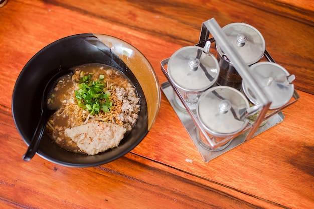 木製のテーブルに黒のカップに入れておいしいスパイシーな麺の近くの調味料ボトル
