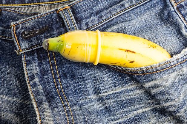 콘돔과 바나나는 청바지 배경에서 안전한 섹스를 할 준비가 되어 있습니다.
