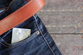 Condom in jeans back pocket with wooden table background