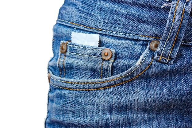 Презерватив в кармане синих джинсов на белом