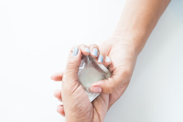 Condom in mano maschile e mano femmina, dare il concetto di sesso sicuro del preservativo su sfondo bianco
