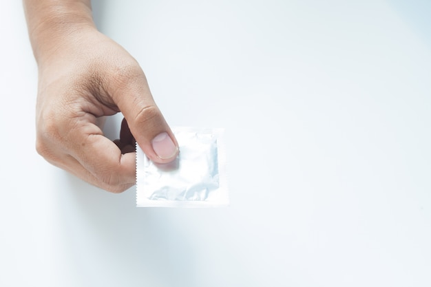 Condom in male hand on white background
