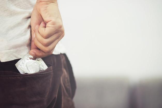 청바지 주머니에 사용할 준비가 된 콘돔 맨, 침대에서 콘돔 안전한 섹스 개념을 제공 감염 예방 및 피임약은 출생률 또는 안전한 예방을 제어합니다. 세계 에이즈의 날, 텍스트를위한 공간을 남겨주세요.