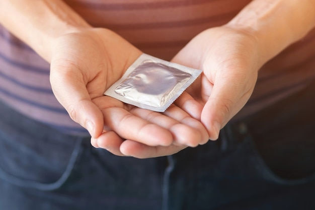 Condom on a man's hand. prevent infection and contraceptives control the birth rate or safe prophylactic.