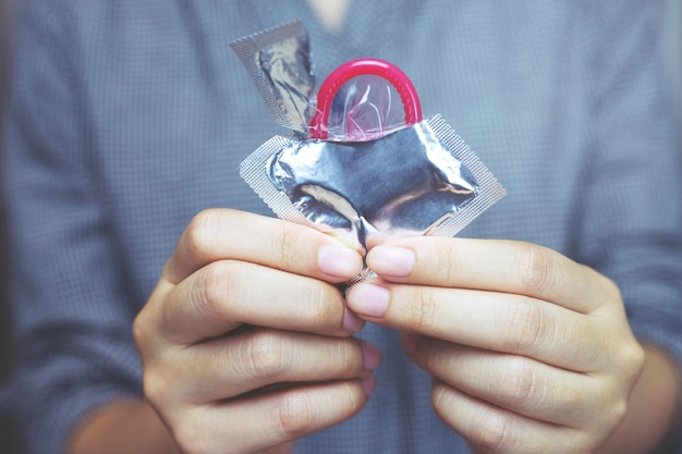 여성의 손에 콘돔을 사용할 준비가되어 있고, 콘돔에 안전한 섹스 컨셉을 침대에 제공하여 감염을 예방하십시오.