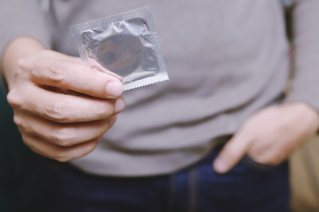 Condom ready to use in male hand, give condom safe sex concept on the bed prevent infection and contraceptives control the birth rate or safe prophylactic