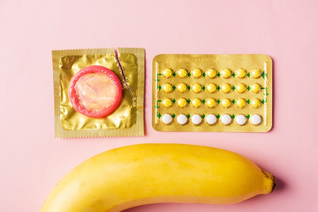Condom on wrapper pack, banana and contraceptive pill, flat lay