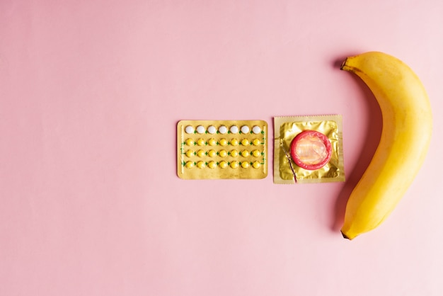 Condom on wrapper pack, banana and contraceptive pill