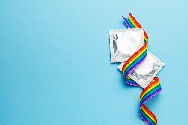 콘돔과 lgbt 무지개 리본 프라이드 테이프 기호. 파란색 배경입니다. 텍스트를 위한 공간을 복사합니다.