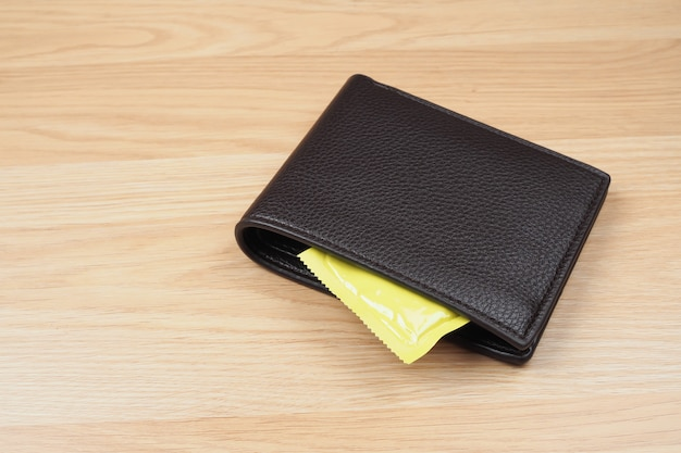 Condoms in black wallet on wooden table background