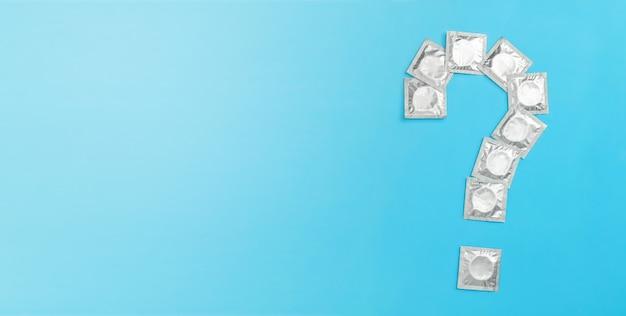 파란색 배경에 물음표 형태로 포장된 콘돔 텍스트 복사 공간