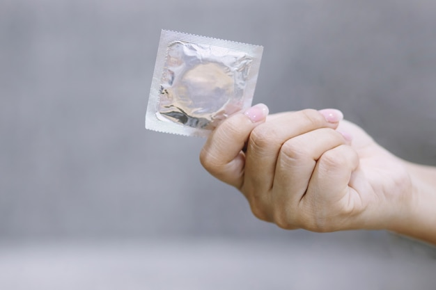 Condoms ready to use in female hand, give condom safe sex concept on the bed prevent infection and contraceptives control the birth rate or safe prophylactic. world aids day, leave space for text.
