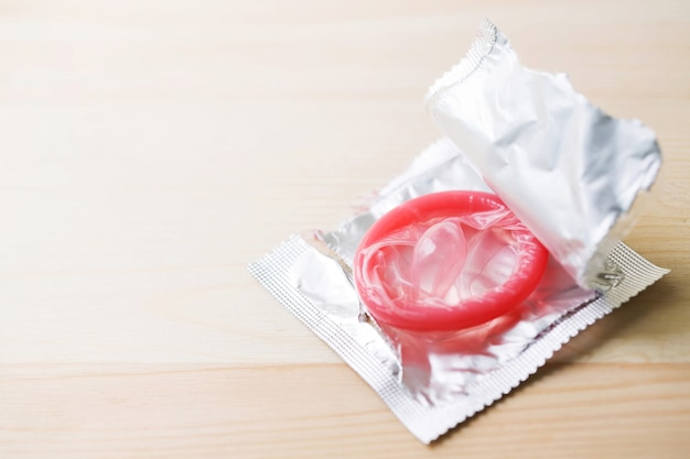Condoms ready to use in female hand, give condom safe sex concept on the bed prevent infection