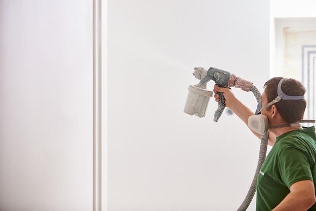 화이트 색상의 스프레이 건으로 condtruction 작업자 그림 벽