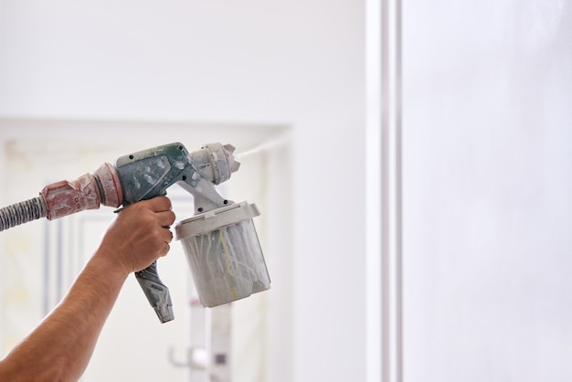 Condtruction worker painting wall with spray gun in white color