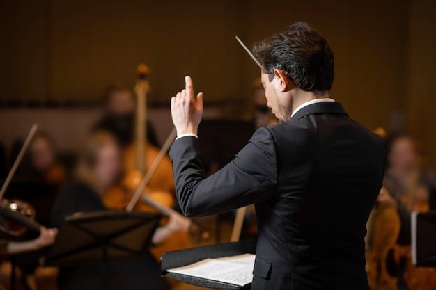 콘서트 홀 배경에 공연자와 심포니 오케스트라의 지휘자