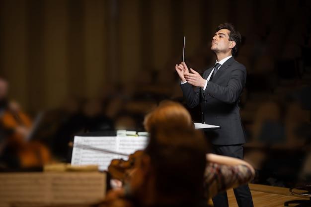 Дирижер симфонического оркестра с исполнителями на фоне концертного зала