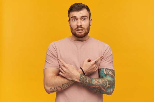 Condused handsome tattooed young bearded man in pink tshirt making x shape with arms and and pointing at both sides by fingers over yellow wall