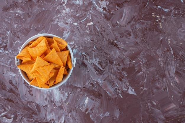 Chip di cono in un secchio, sul tavolo di marmo.