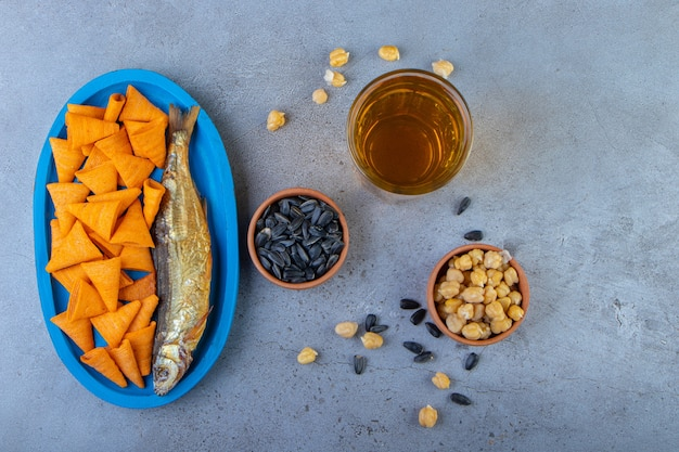 Cone chips and dried fish on a wooden plate on a towel , on the marble surface.