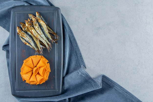 Cone chips and dried small salted sprat on a tray on the pieces of fabric , on the marble background.