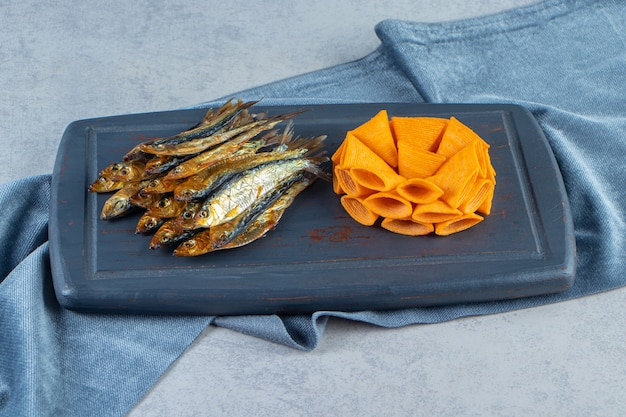 Cone chips and dried small salted sprat on a tray on the pieces of fabric , on the marble surface.