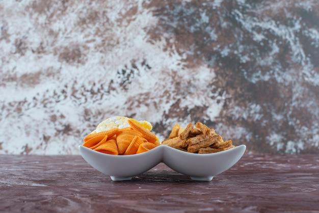 대리석 테이블에 있는 그릇에 빵 부스러기가 있는 콘 칩.