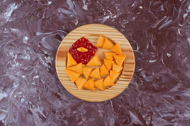 大理石のテーブルの上に、木の板にケチャップを入れたコーンチップス。