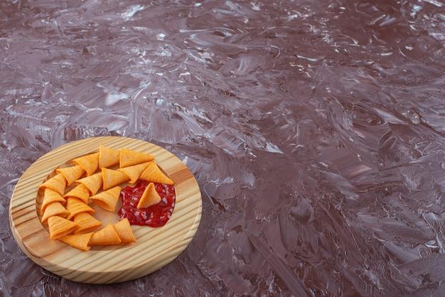 대리석 테이블에 나무 접시에 케첩이 든 콘 칩.