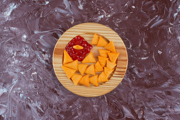 Cone chips with ketchup in a wooden plate , on the marble table.