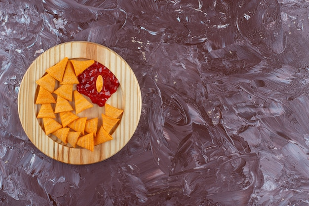 Chip di cono con ketchup in un piatto di legno, sul tavolo di marmo.