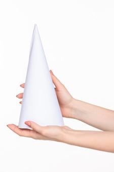 Il cono in mani femminili su spazio bianco
