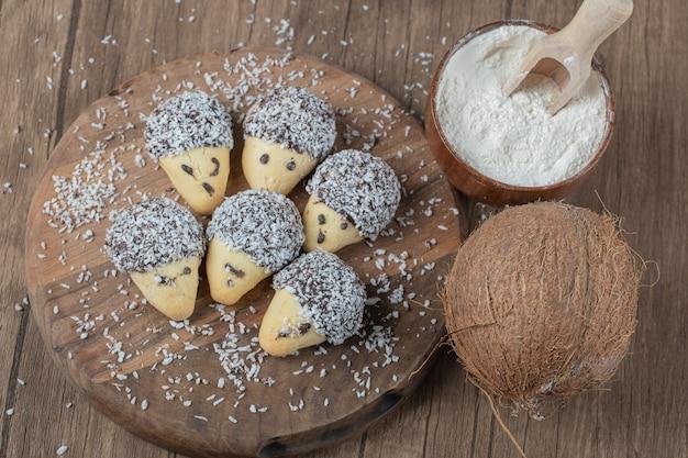 木の板にチョコレートのトッピングとココナッツパウダーが入った円錐形のクッキー。