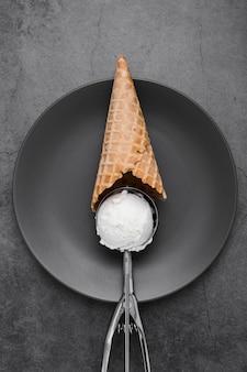 Cone with vanilla ice cream scoop