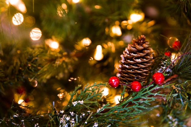 Cone with yellow lights on green branches of christmas tree. new year decorations