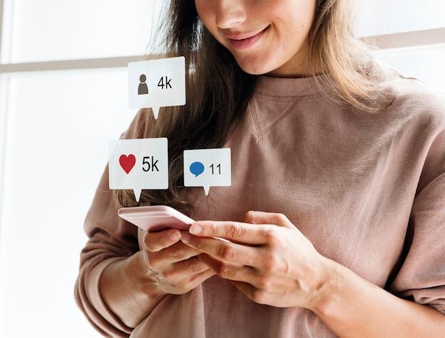 女性はスマートフォンソーシャルメディアのconecptを使用して