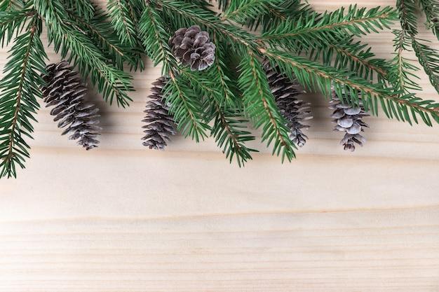 Шишки и зеленые еловые ветки на деревянном фоне. концепция празднования нового года с копией пространства