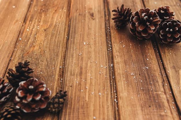 Конусы и снег на коричневом дереве.