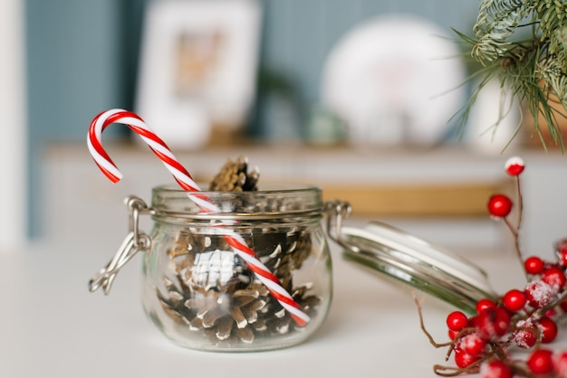 Cones in a glass jar and a lollipop cane close-up, christmas decor