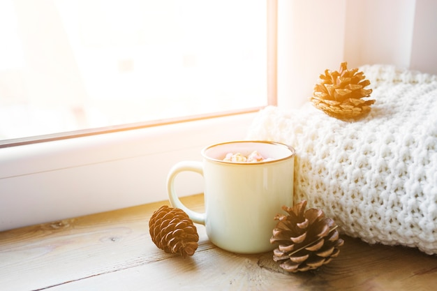 Cones and hot chocolate near scarf and window