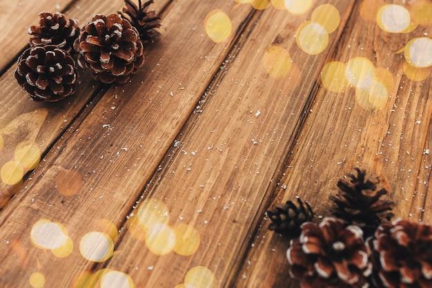 茶色の木にコーン、雪、黄色のボケ味。