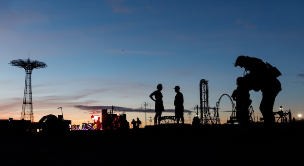 Пляж кони-айленд в нью-йорке. силуэты людей и вышка для прыжков с парашютом на фоне заката