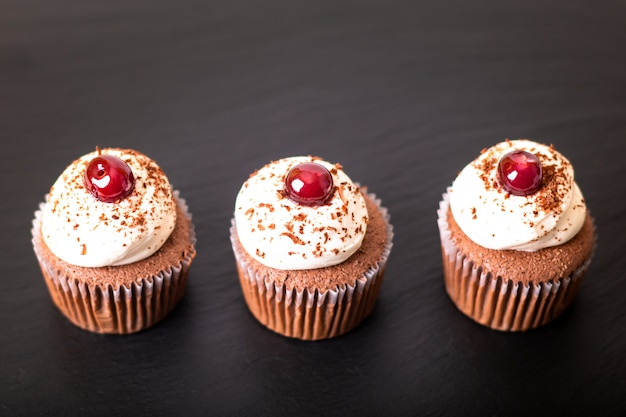 Confection dessert homemade black forest cupcake on a black slate stone plate