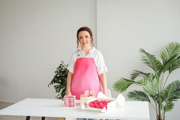 白いテーブルの上のおいしいデザートの横にポーズをとるピンクのエプロンを身に着けている菓子職人