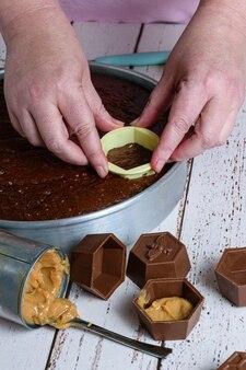 Кондитер нарезает кусочек бразильского медового торта и помещает в шоколадную форму, наполненную дульсе де лече (вертикальное фото).