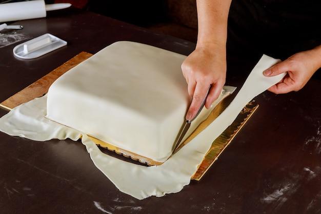正方形のケーキに白いフォンダンを切る菓子職人。ケーキの作り方。