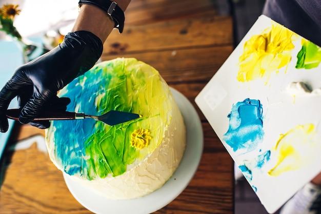 お菓子屋さんがカラフルなクリームでケーキを飾ります。パターンの手作りケーキ。