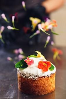 과자 장수는 부활절 케이크를 섬세한 꽃으로 장식합니다.